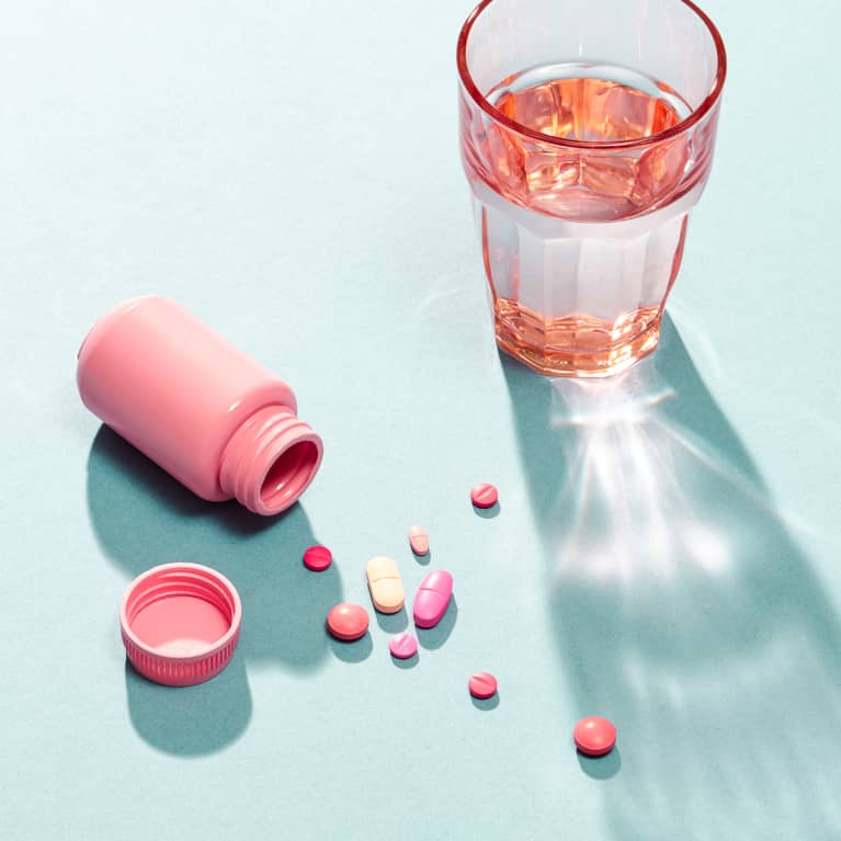 Pills, Capsules, and Vitamins on a Surface with a Glass of Water