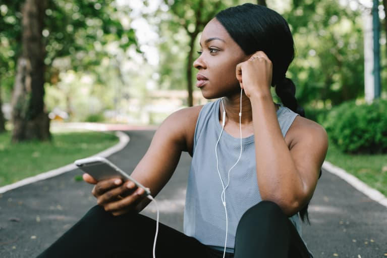A young black woman using her smart phone while listening to music and resting from a workout run in the park on the road amidst green grass and trees
