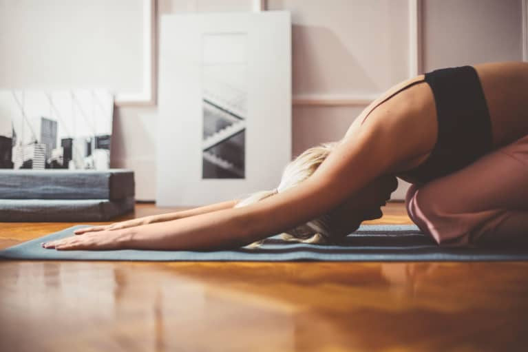 Woman doing yoga to lower cortisol