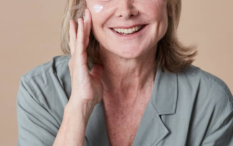 Unrecognizable Woman In Her 50s Applying Moisturizer to Her Face