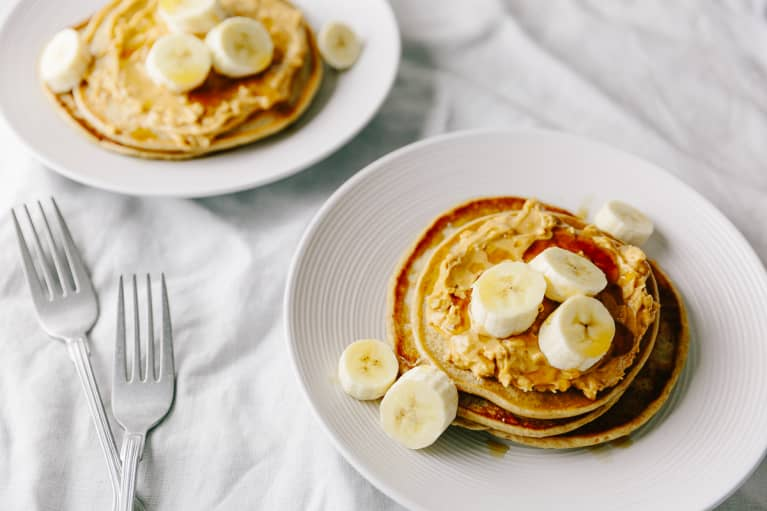Two Plates Of Vegan Pancakes With Peanut And Banana