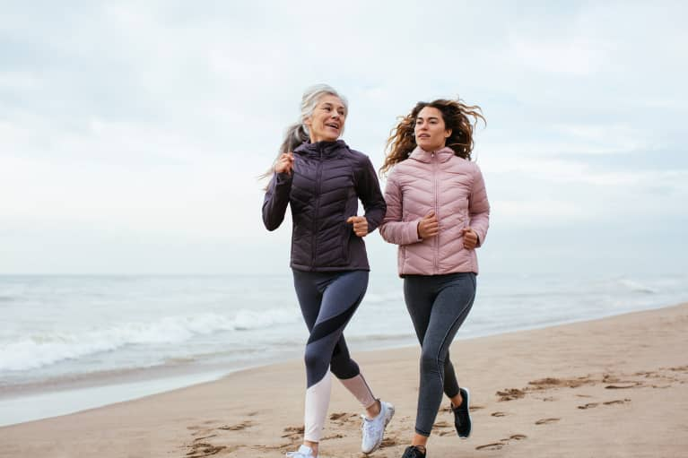 Older woman and her daughter running on the beach