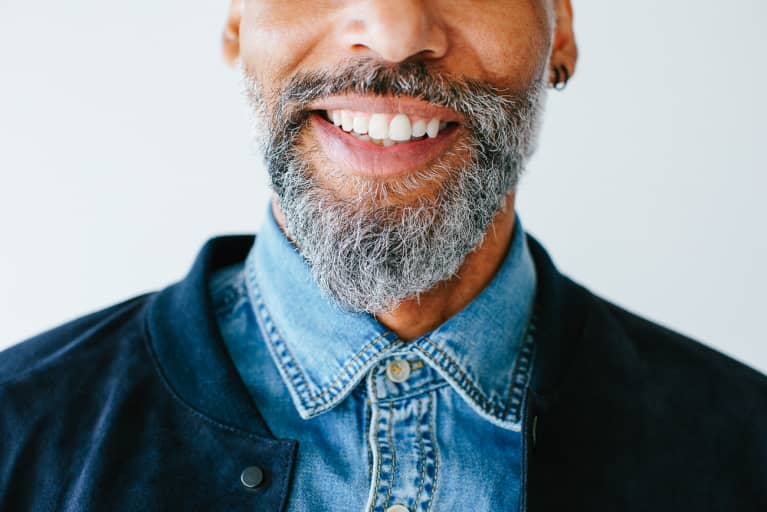 Closeup portrait of a cool man with a beard smiling on white