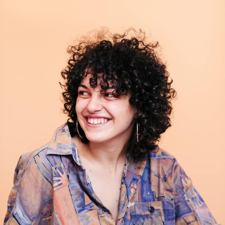 Women smiling with curly hair on a tan background