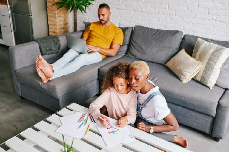 miling mother and her little daughter drawing pictures together at their coffee table with dad relaxing on the living room sofa