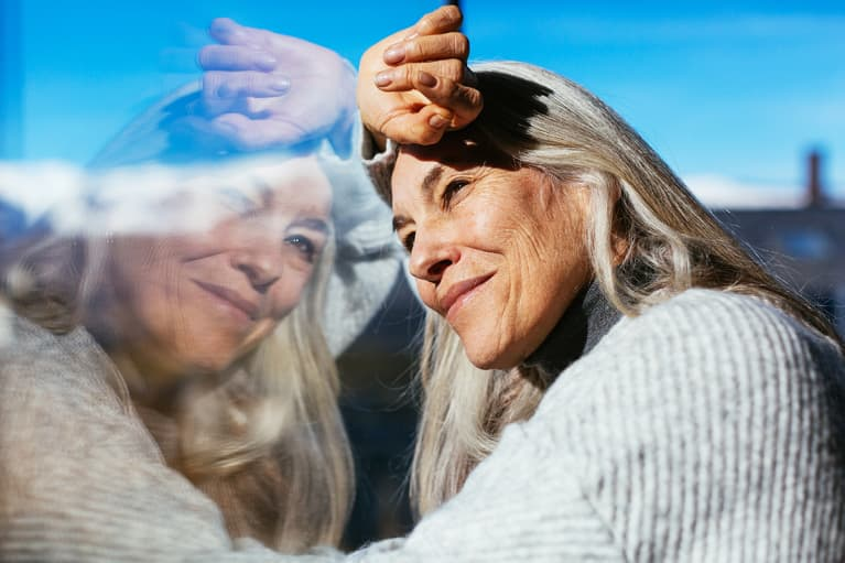 Cheerful mature lady with gray hair smiling and looking away while leaning on window and enjoying sunny day at home