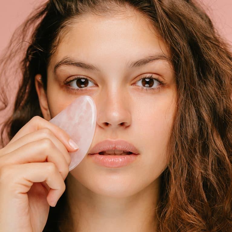 Woman Using a Rose Quartz Gua Sha on Her Face
