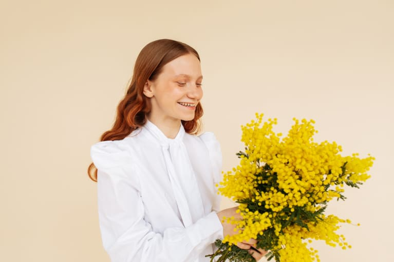Young woman holding a bunch of yellow flowers