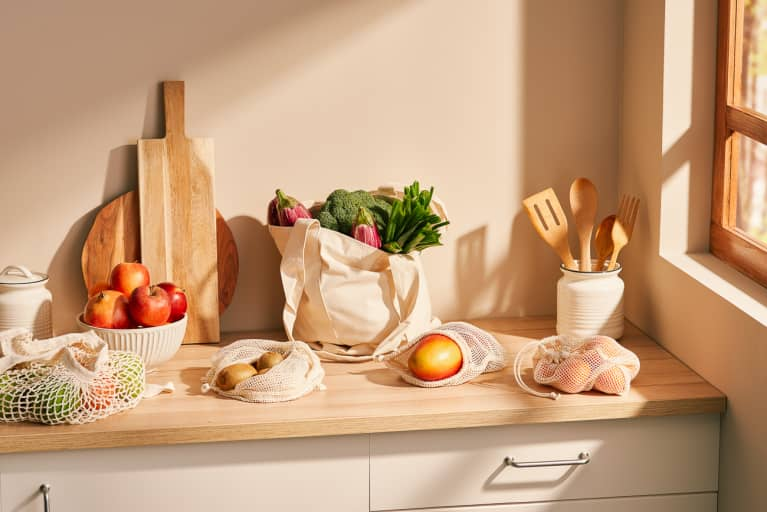 Bunch of various ripe fruits and vegetables in zero waste sacks placed on counter near wooden kitchenware against beige wall in contemporary kitchen