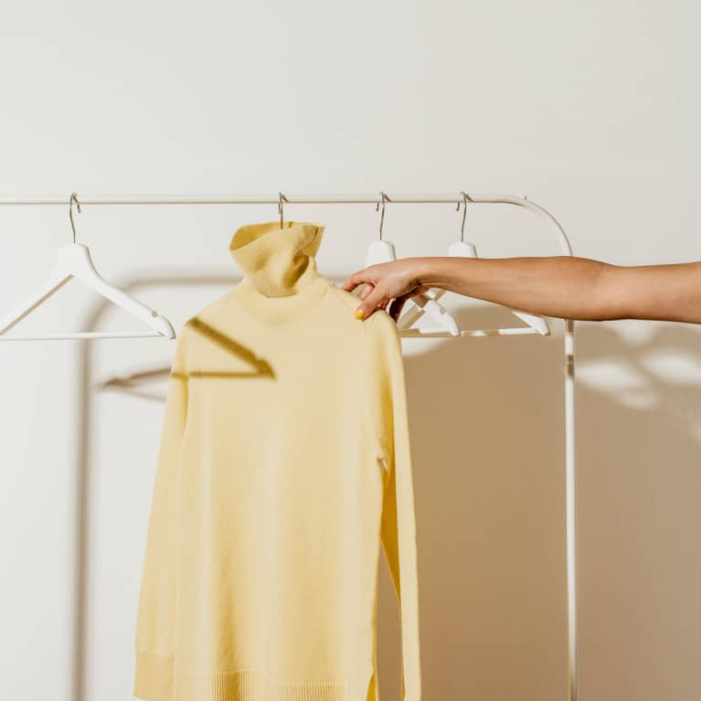 Hand Reaching for a Yellow Turtleneck in a Minimal Closet