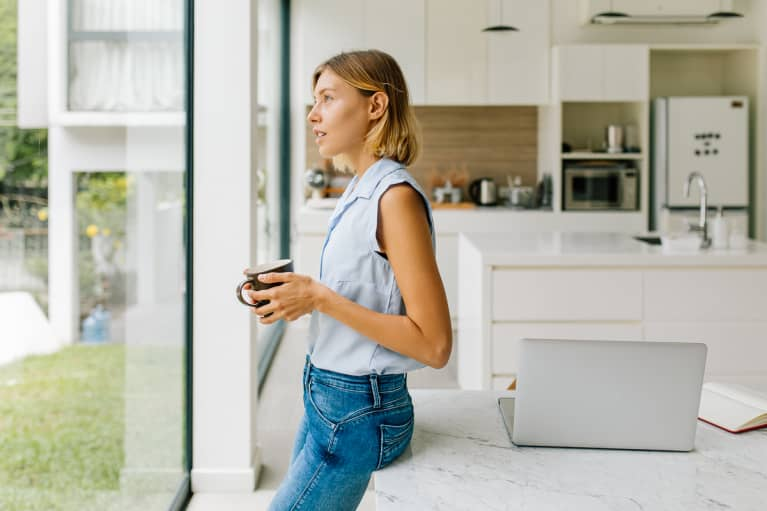 Young Woman Leaning Against Table with a Cup of Coffee Looking Out the Window