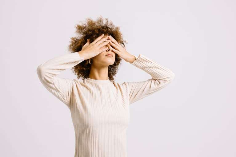 Stressed Woman with Hands Over Her Eyes in a Studio
