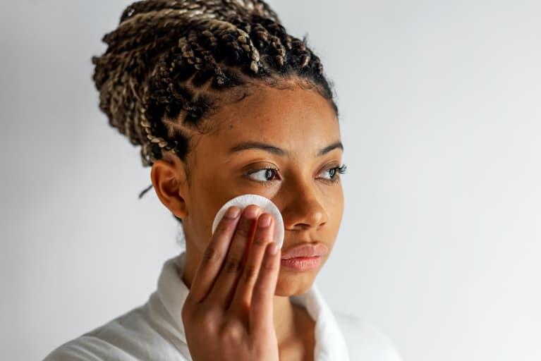 Black Woman Applying Tonic On Face
