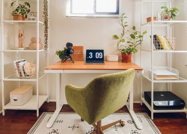 clean desk with two bookcases on either side and a green swivel chair