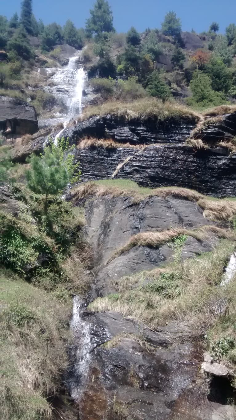 tall waterfall against tree-lined landscape