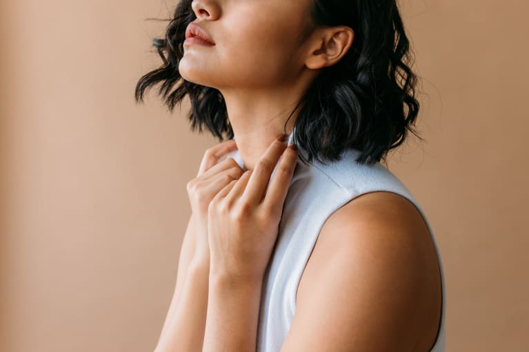 Woman grasping her shirt collar in contemplation