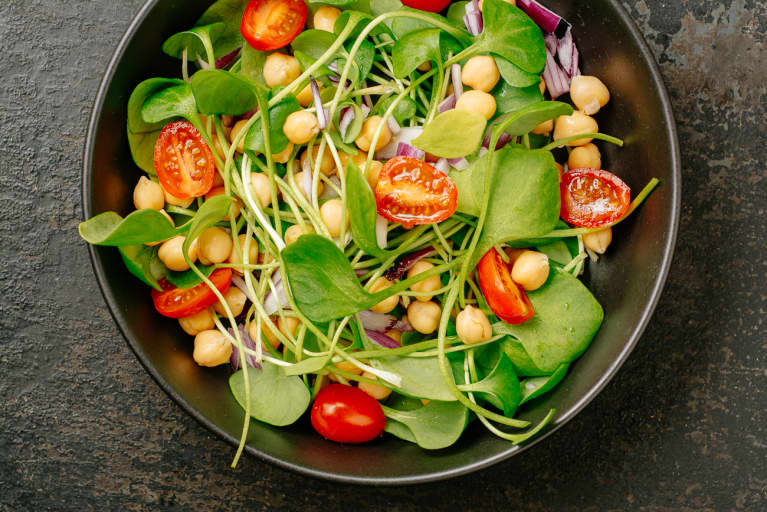 Vegan salad with purslane, chickpeas, tomatoes, and red onion