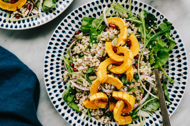 Baked delicata squash over a bed of spinach and quinoa with red onion and pomegranate seeds.