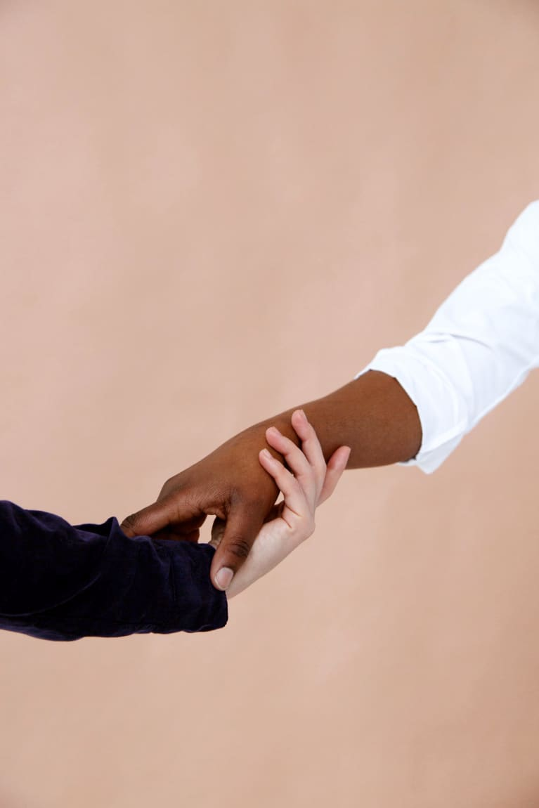 An image of two people holding hands, letting go of each other.