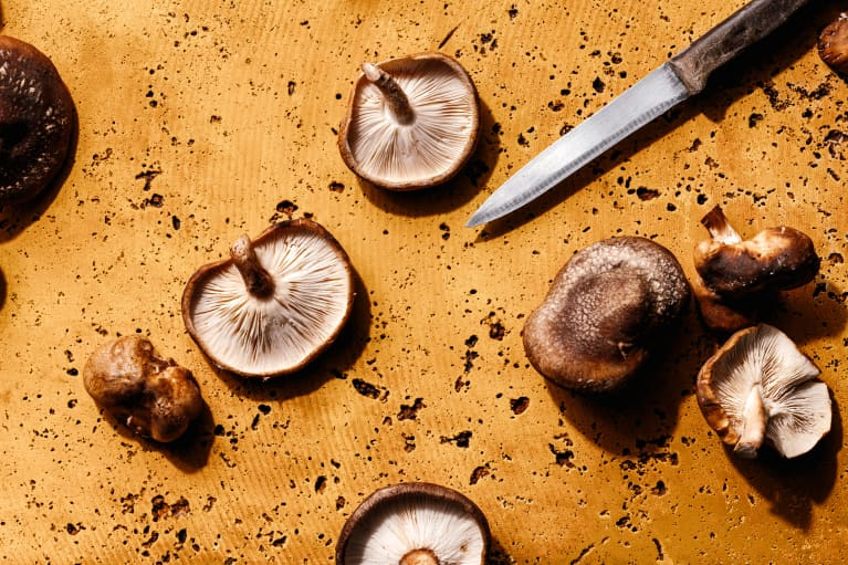 shiitake mushrooms on mustard yellow background with knife