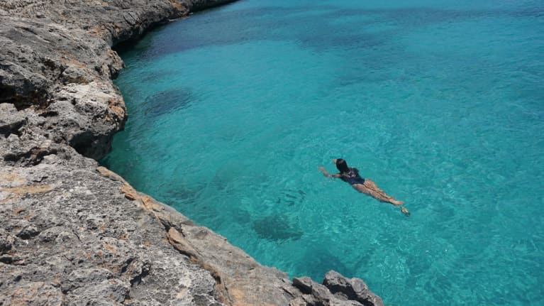 woman swimming in crystal blue waters