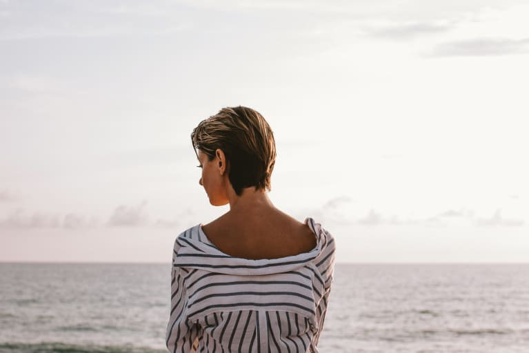 Image of a woman looking out at the ocean thinking.