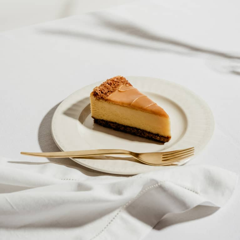 Caramel cheesecake on a plate in a minimal setting