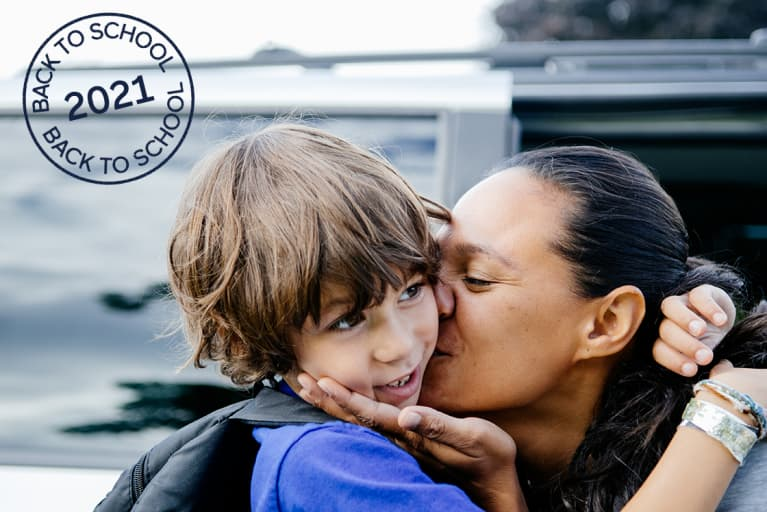 Mother kissing her son on the cheek and cupping his chin with her hand as she drops him off for school.