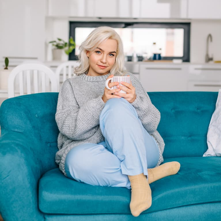 Beautiful blond woman spending her day off at home, sitting on the couch, drinking coffee