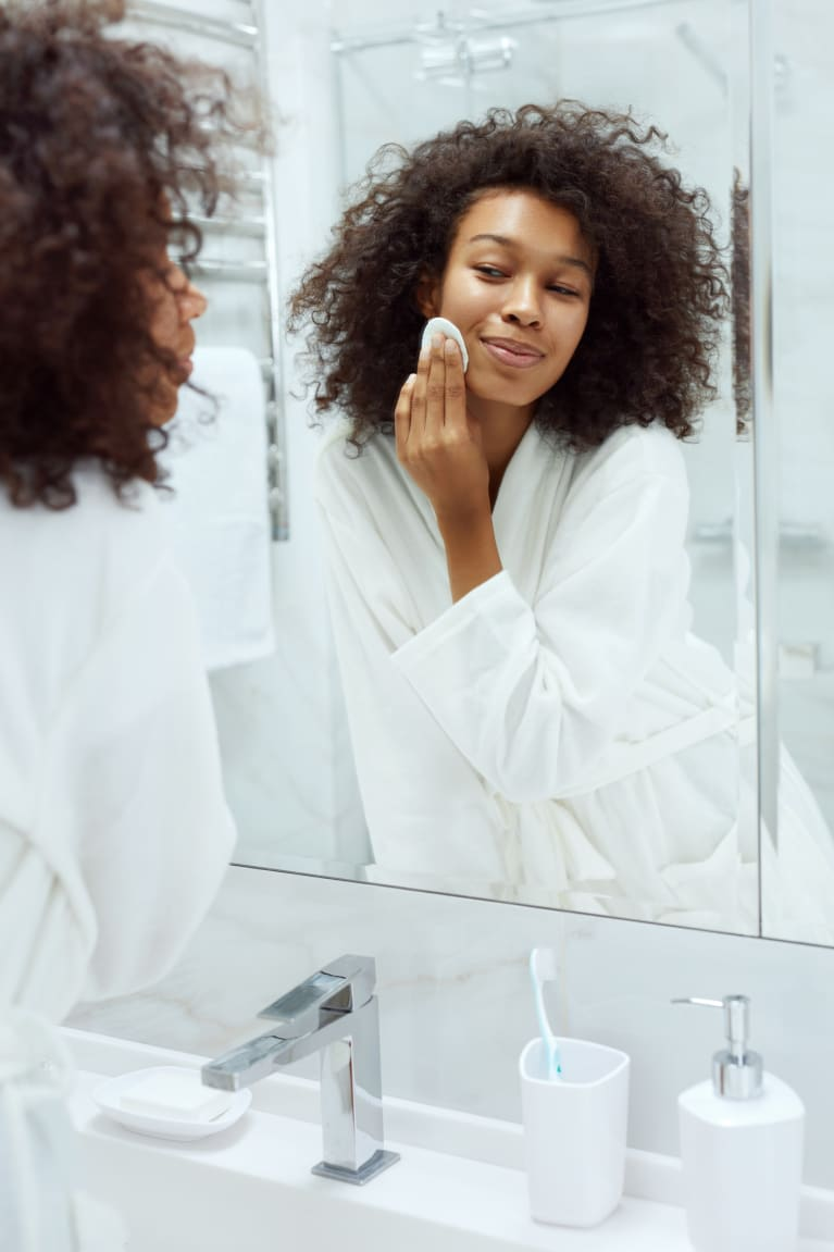 Woman Doing Skincare Routine in the Mirror