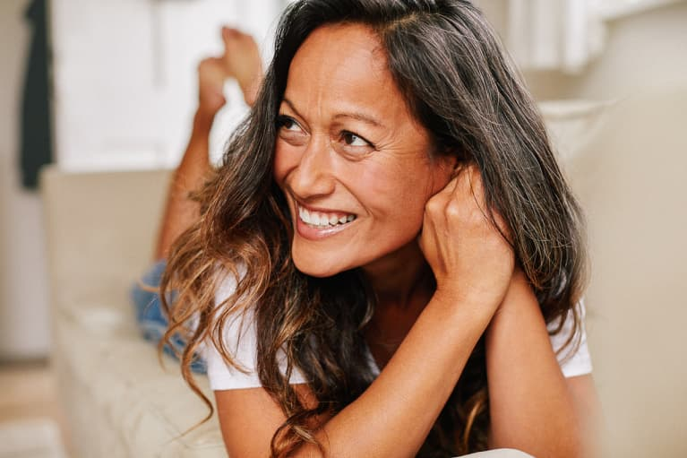 Woman in Her 40s With Great Skin, Smiling on Her Living Room Couch
