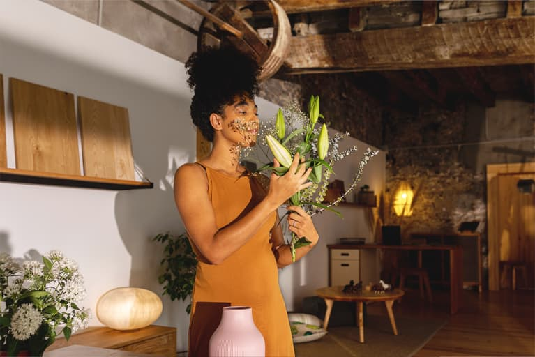 woman in dress smelling a bouquet of flowers in a chic home