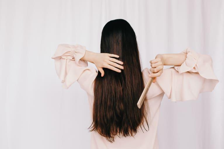 woman brushing long brown hair