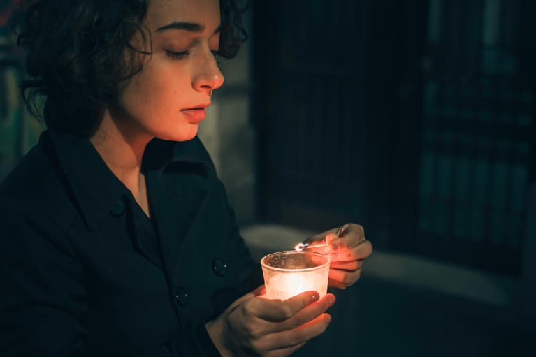 Woman Lighting A Candle In The Darkness