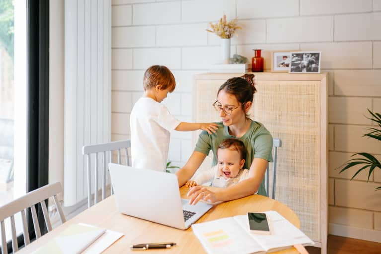 Busy concentrated mother using laptop with weepy baby on the lap near active kid on a chair at modern home