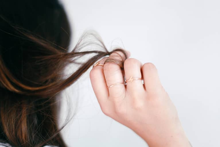 Woman Holding A Piece Of Her Hair In Her Hand
