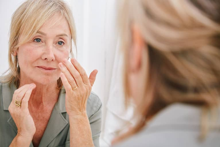 woman in her 60s looking at her skin