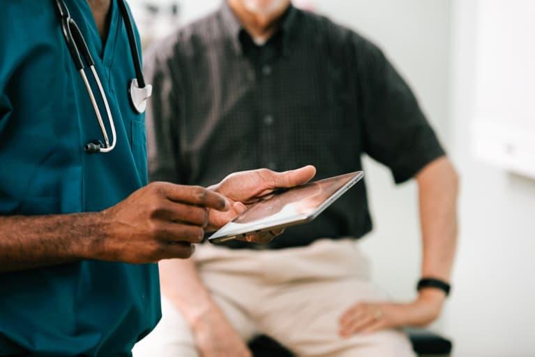 Doctor Enters Information Into Digital Tablet