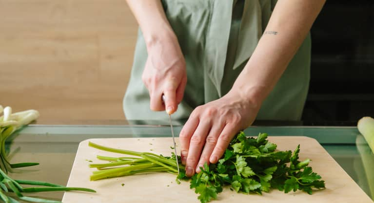 Unrecognizable Woman Cutting Off Parsley Stems