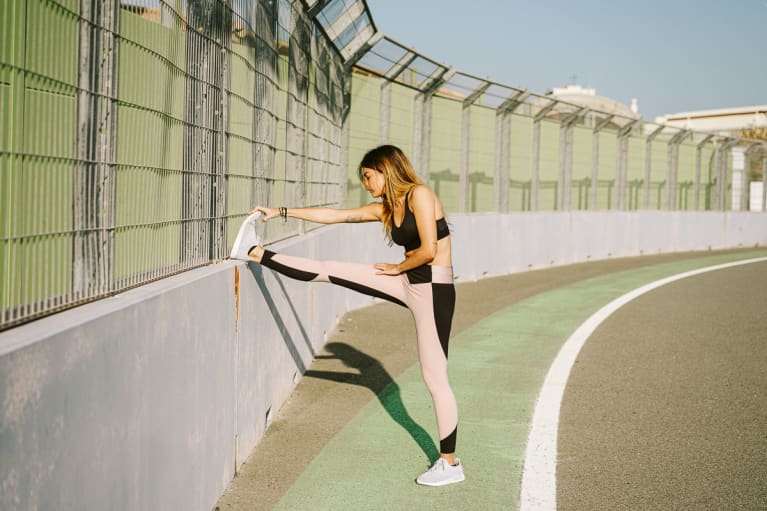Woman Stretching Hamstring on an Outdoor Running Track
