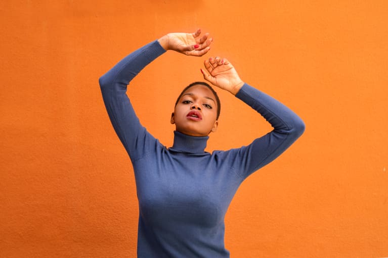Portrait of a woman in a blue sweater on an orange background