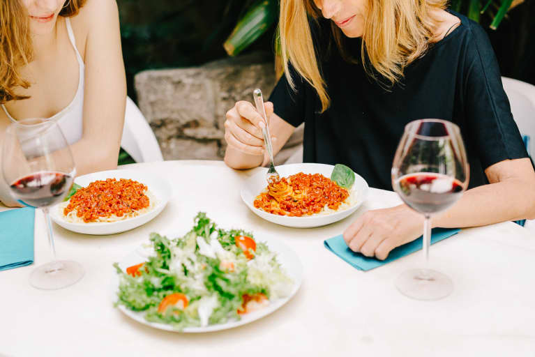 Women Sitting at Restaurant Eating Spaghetti and Drinking Wine