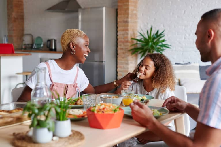 family eating nutritious meal together at dinner table