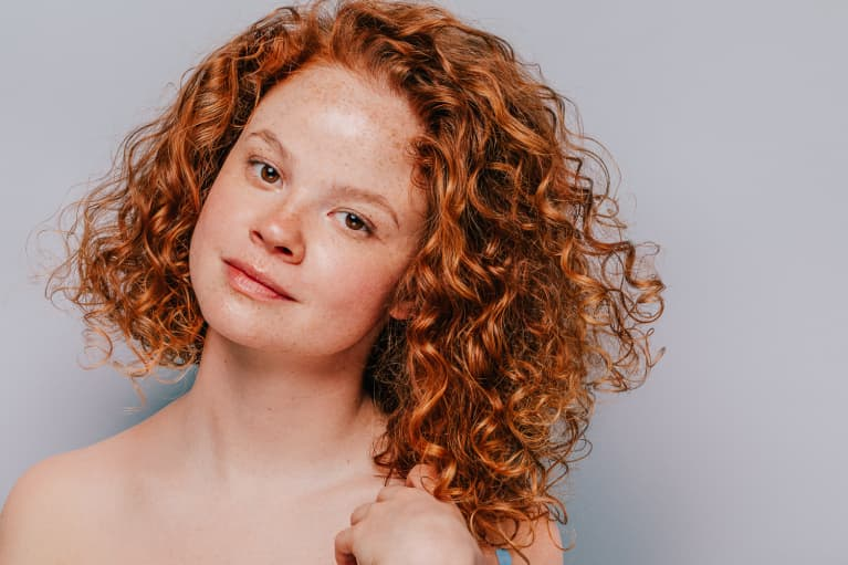 Young Woman With Freckles and Red Curly Hair