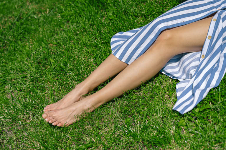 Unrecognizable Woman's Legs on Grass