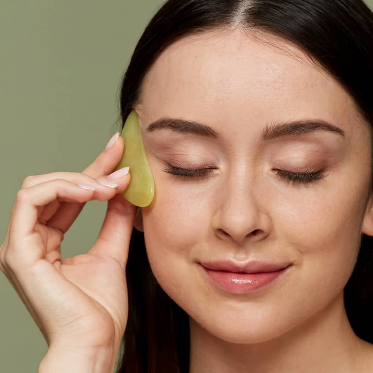 a woman using a gua sha stone on a green background