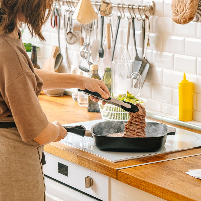 Woman Cooking a Steak in a Cast Iron Skillet