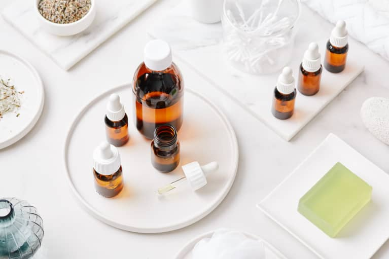 Small glass bottles of essential oil surrounded by beauty and personal care products