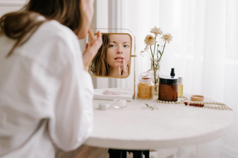 woman sitting at a vanity applying lip balm in mirror