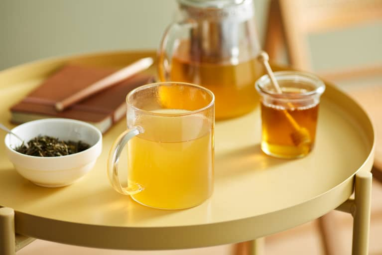 Close-up of sweet herbal tea with honey served in glass mug on round metallic table with bowl of dry leaves, notebook, jar of honey and glass teapot